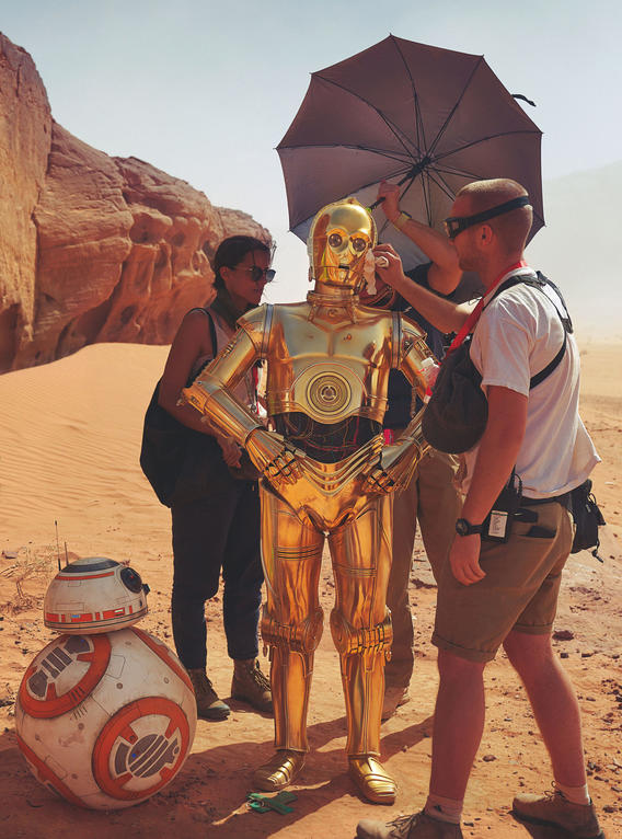 Members of the crew shade and shine Anthony Daniels (C-3PO), the only cast member to appear in all nine of the Skywalker films, while BB-8 looks on